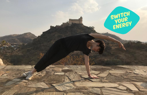 Woman doing yoga on top of hill, switch your energy