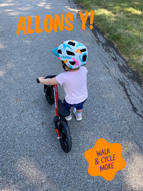 Small child riding small red bike to walk and cycle more