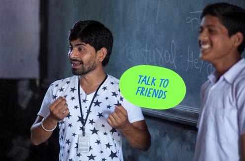 Two teachers stood in front of a chalkboard