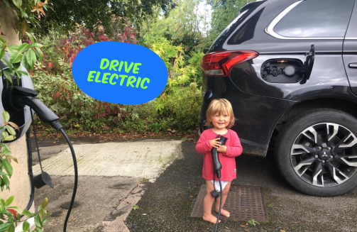 Small child holding an electric charger next to a black electric car