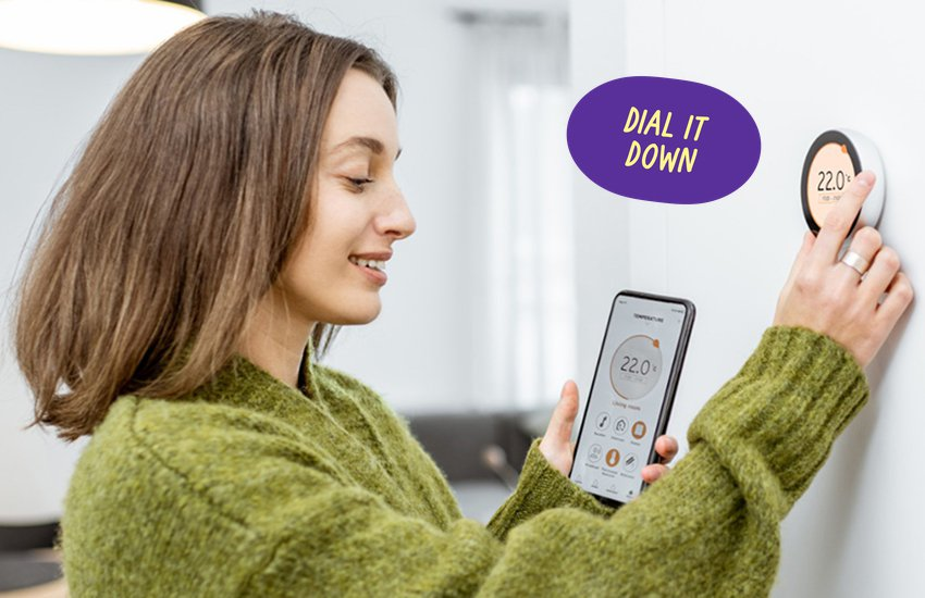 Woman turning heating down with Dial It Down sticker on