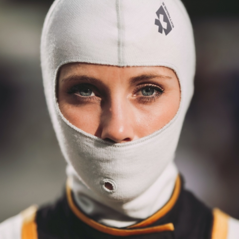woman in a driver's mask looking directly at the camera